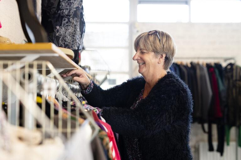 Vrouw zoekt iets uit in kledingbank