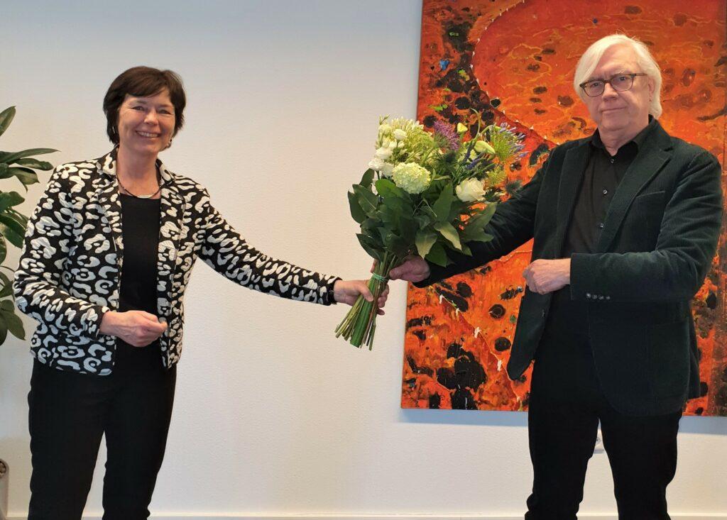 Afbeelding Henriëtte Hulsebosch overhandigt bloemen aan Bert van Alphen